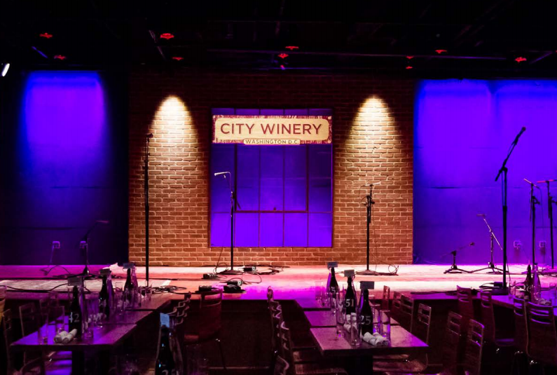 Image of a stage awash in purple and blue lighting,with dining tables arranged. Sign on the wall has City Winery logo.